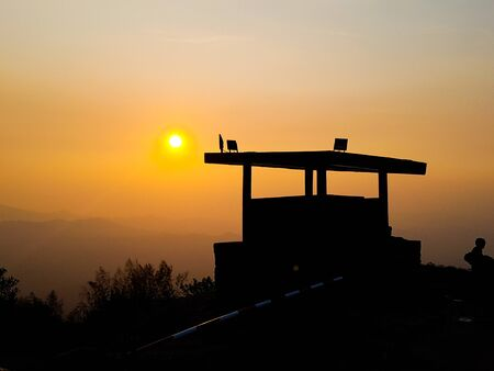 silhouette of military post  on mountain peak against sunset