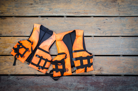 orange life vest on wooden background Stock Photo