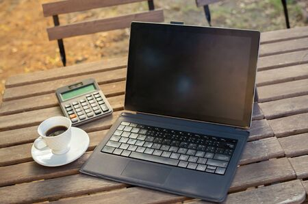 blank laptop with coffee on wooden table