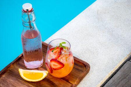 orange italian soda with fresh strawberry on pool side Stock Photo