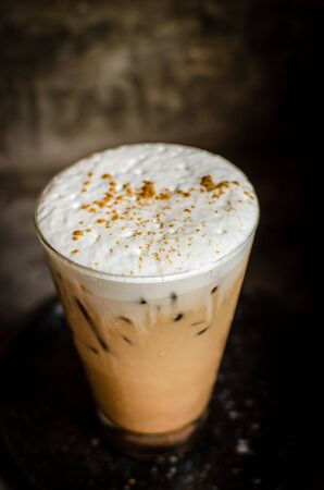 iced cappuccino with cinnamon on top in low-key