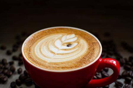 hot latte art in red mug against coffee beans Stock Photo