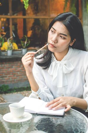 business woman in white shirt working in cafe