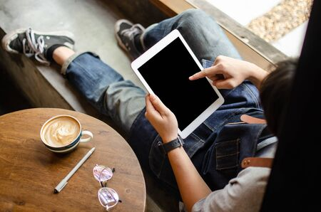 man using tablet on wooden table