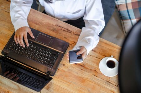young woman using laptop on wooden table Stock Photo