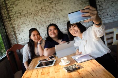 group of business woman taking selfie in cafe
