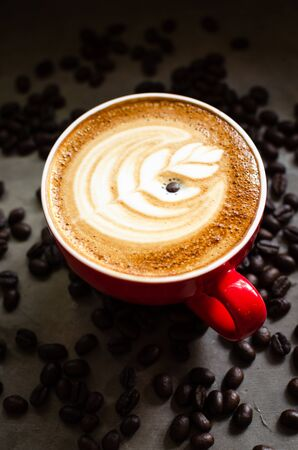 hot latte art in red mug against coffee beans Stock Photo - 126175917