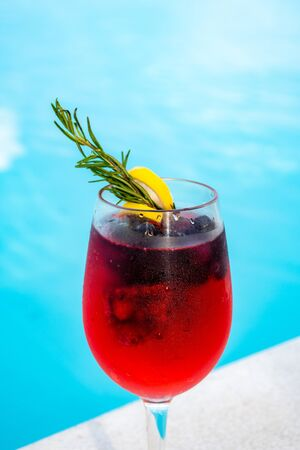 iced mixed berry cocktail against pool side