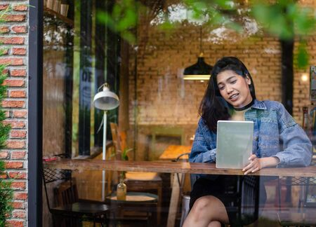 happy asian woman using tablet in cafe Stock Photo