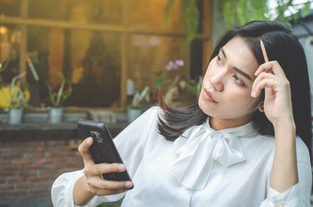 business woman in white shirt using smartphone in cafe