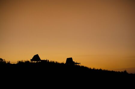 silhouette of huts on a hill against sun set background in thailand Stock Photo - 126179074