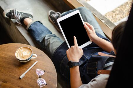man using tablet on wooden table Stock Photo - 126179076
