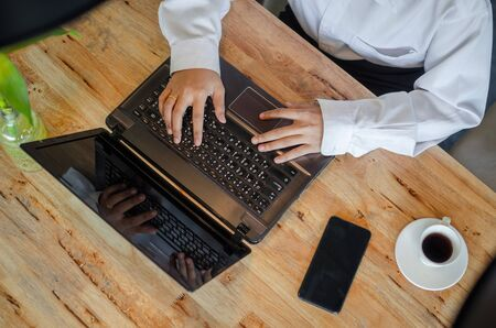 young woman using laptop on wooden table Stock Photo - 126179308