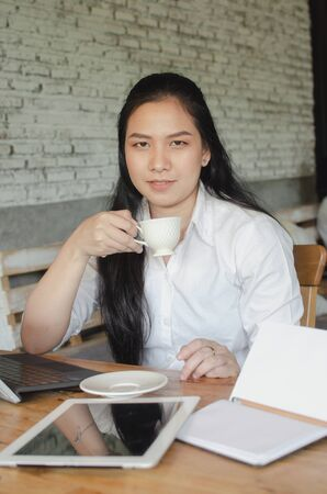 young woman drinking coffee while working in cafe