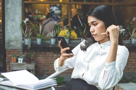 business woman in white shirt using smartphone in cafe Stock Photo - 137364269