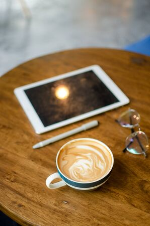 coffee mug with modern working tools on wooden table