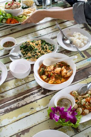 thai food on wooden table with people's hand enjoy eating it Stock Photo