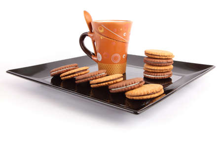 black dish: Cup of tea with biscuits on black Dish, breakfast