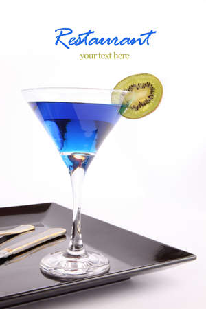 black dish: Blue drink on in a cocktail glass with Kiwi fruit in blank black dish ,  fork and knife isolated on white background with your text here