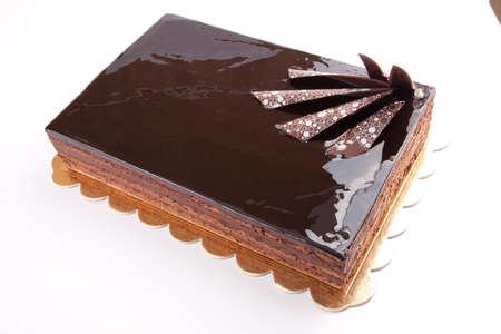 Chocolate glossy dark Cake on white stuffed with nuts photo