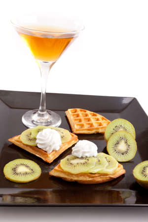 Kiwi Tart Slices with Fresh Juice In Cocktail Cup on Dish photo