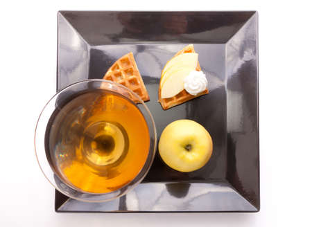 Apple Tart Slices with Fresh Juice In Cocktail Cup on Dish photo