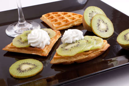 Kiwi Tart Slices with fresh vanilla cream on black dish photo