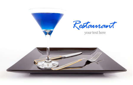 black dish: Restaurant Design Blue drink in a cocktail glass in black dish with fork and knife  Stock Photo