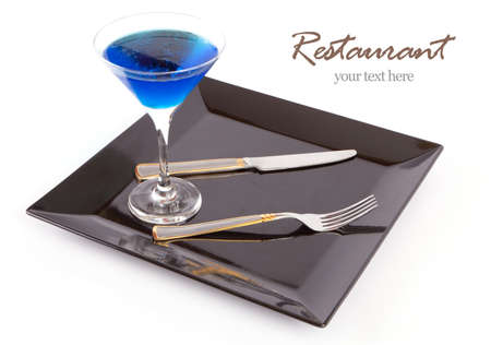 Restaurant Design Blue drink in a cocktail glass in black dish with fork and knife  photo