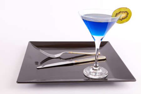 black dish: Blue drink in a cocktail glass in black dish with fork and knife