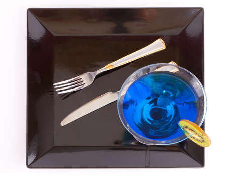 Blue drink in a cocktail glass in black dish with fork and knife  photo