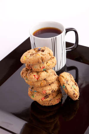 Cup of tea with cookies with colored chocolate on black dish photo