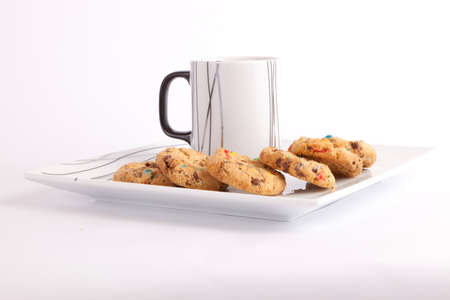 Cup of tea with cookies with colored chocolate on white dish photo