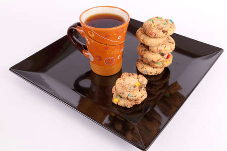 Assorted cookies in black plate and brown mug of coffee photo