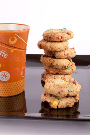 Assorted cookies in black plate and brown mug of tea photo