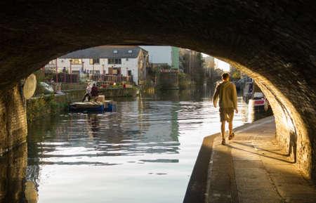 The man walks under the bridge along regents canal Stock Photo