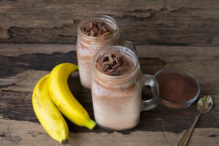 Banana and chocolate smoothies milk put a glass on a wooden background.