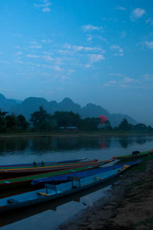 tranquille: Kayaks on the Nam Song River in Vang Vieng, Laos at Sunrise