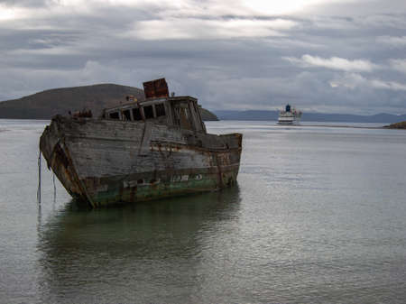 ship wreck: Old ship wreck at shore with a cruise ship in the background at New Island Falkland Islands Stock Photo