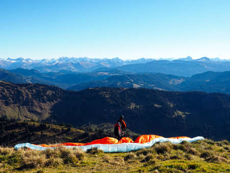 glide: Paraglider in the Bavarian Alpes in front of mountain panorama and blue sky
