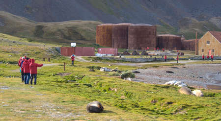 king edward: Tourists in front of old rusting boilers and whale oil storage tanks at the old whaling station in Grytviken, South Geoergia