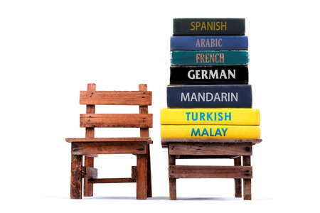 Dictionary books stacking on a table. White background.