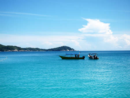 Perhentian Island Resort. Beautiful nice turquoise coloured sea view with floating boats. Stock Photo