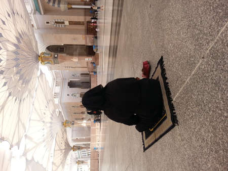 MADINAH, SAUDI ARABIA - AUGUST 20: A women performing prayer at Prophet Muhammad Mosque on August 20, 2015 in Madinah, Saudi Arabia. Editorial
