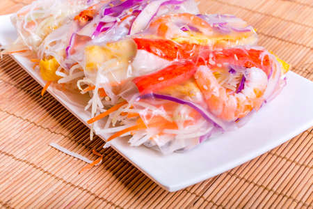 Vietnamese spring-roll on a white plate on a mat background