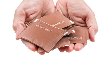 eliminate: Hand filled with brown sugar packs. Isolated on white background.