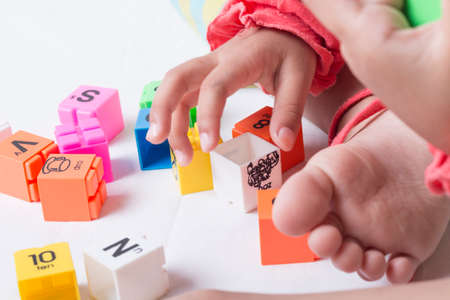 Kids hands plug and play the alphabets toys. White background. Stock Photo