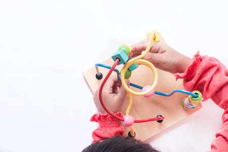 Kids hands playing with different shapes of blocks and moving it around its track. Stock Photo