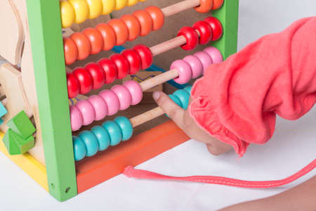 Kid learns on mathematic concept using colorful counting beads or abacus. Stock Photo