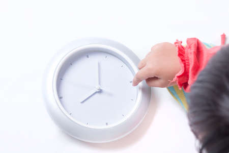 Kids fingers pointing towards the digital clock. Top view.